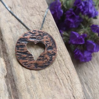 """Round copper pendant. Textured and oxidised to enhance the look of the texture. A heart has been handpierced with a jewellers saw from the centre of the pendant. Easy to wear for day or evening. Matched with an silver chain that has been given an oxidised look. Chain is 18"""" long"""