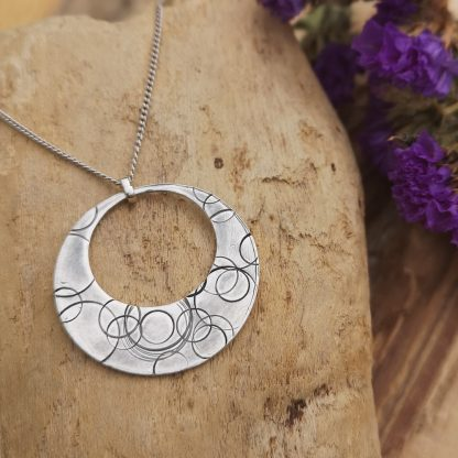 Handmade by Tamala presents Bubbles Galore a silver circular pendant with a circle cut out. Hand tools have been used to make marks in the metal. Finished with a patina to accent the marks