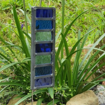 Blue glass garden stake in greenery
