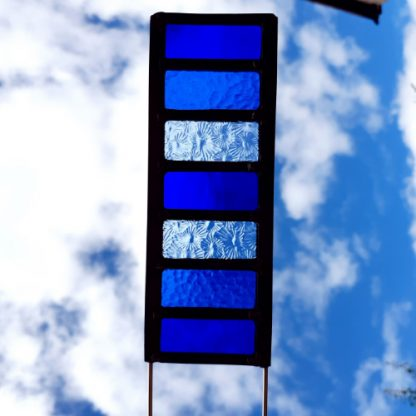 Blue stained glass garden stake held up to sky