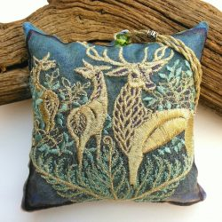 A piece of weathered wood props up this square lavender pouch in teal blue colours, featuring a story within the stitches, of a proud Stag looking out with two hinds behind in amongst the bracken and bushes , who are looking at each other.