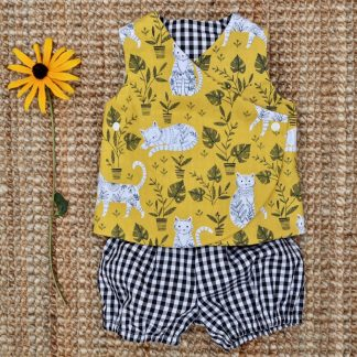 Baby outfit of wrap over tunic style top and matching bloomers. Top is mustard yellow with a cat print. The top lining and bloomers are black and white checked gingham