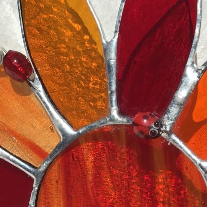 close up image of ladybird bead on stained glass sunflower