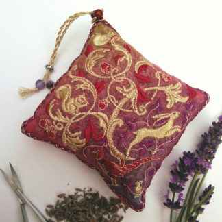 on a white plain background an embroidered design portrays the flora and fauna of an Oak woodland ,featuring creatures in gold stitches with red and violet coloured threads and fabric . displayed next to some lavender flowers and a pair of scissors for scale.