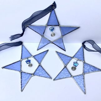 A trio of pale blue stained glass stars with wire and bead embellishment