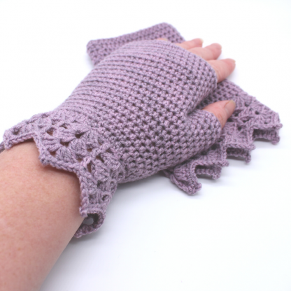 A pair of lavender crochet gloves on a white background