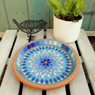 Mosaic birdbath with a bohemian mandala style design radiating shades of aqua, turquoise, sky and sapphire blues.