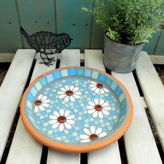 Mosaic bird bath with a white daisy design on a pastel blue and green background