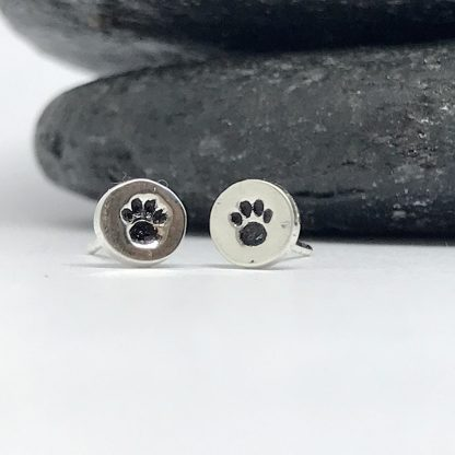silver earrings with a black paw print sitting in front of slate stones on a white background