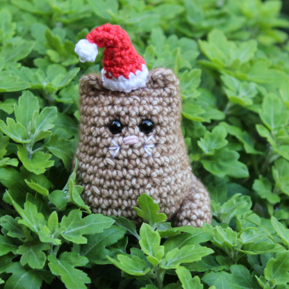 small crochet cat with santa hat on