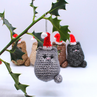 Cat Christmas decoration hanging from a sprig of holly