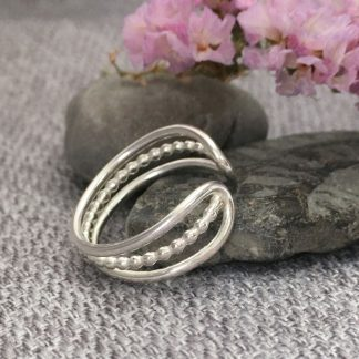 Triple band silver ring with open curved front. Two bands plain one bubble beaded. Adjustable size as open fronted