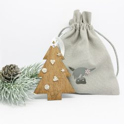wooden Christmas tree with earrings as baubles next to fir cone and gift bag on a white background