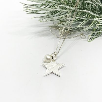 silver star and freshwater pearl on a silver chain next to green leaves on a white background