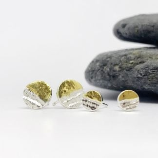 small and medium sized silver and gold earrings in front of. agrey stone on a white background