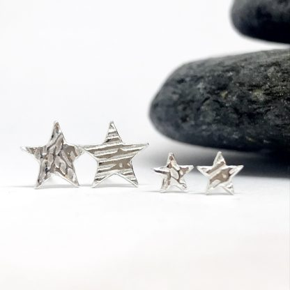Silver star earrings in two sizes with an abstract texture sitting in front of a grey stone on a white background