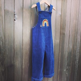 Dark blue corduroy dungarees with a rainbow on the front pocket displayed against a wood panel background