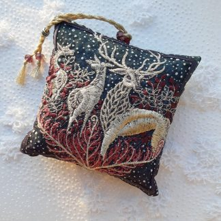 Dark coloured scene of woodland in dark coppery brown, with snowflakes falling on a square shaped pillow lavender bag on white snowy back ground of snowflakes shaped
