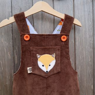 Dark brown dungarees with a fox appliqué on the front bib pocket and bright orange buttons