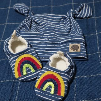 Blue and white striped baby hat with matching soft shoes. Hat has two knots on the top of the head & the shoes feature an appliquéd rainbow