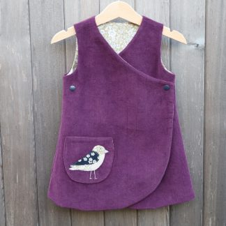 Plum corduroy girl's dress in a wrap over style with a green floral lining and a bird appliqué on a front pocket
