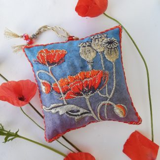Red poppies and seed heads are featured on a blue fabric squared shaped lavender bag with red borders and a gold hanging loop and beads out of the top. Displayed next to real red poppies flowers.