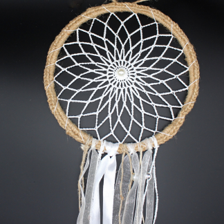 White dreamcatcher against a black background