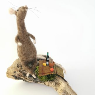 wool sculpture of a rat sat on driftwood eating a picnic