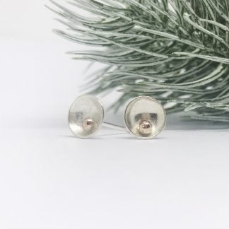 silver earrings with a sphere of rose gold infant of a fir on a white background