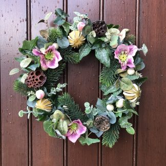 Full Christmas wreath with greenery, lotus pods and pink Christmas roses