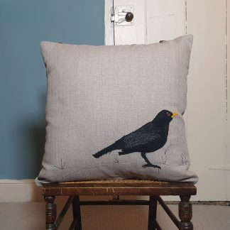 Blackbird applique cushion on natural linen with free motion embroidery