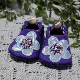Purple tweed baby shoes with shiny appliquéd flowers on the uppers