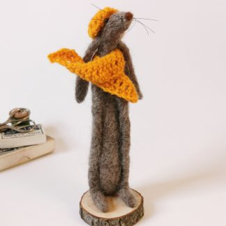 wool sculpture of a hare wearing yellow hat and scarf mounted on wood