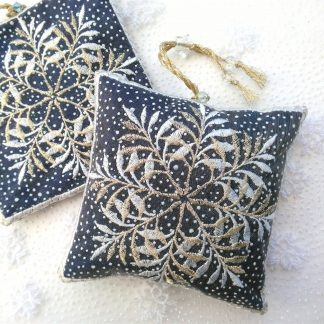 A white and silvery gold embroidery of a snowflake embroidered onto a blue grey spotty fabric of a square lavender bag with beads on a white background of a snowy fabric