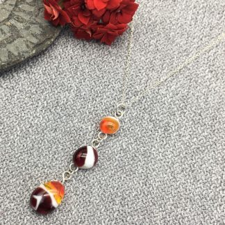 Three fused glass cabochons in red, yellow and white set on a silver spiral setting on a silver chain