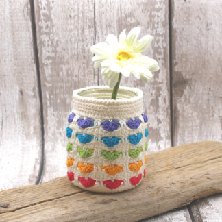 a jam jar covered in a pattern of crocheted rainbow hearts