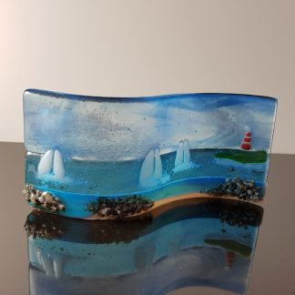 I Saw Three Ships is a small, handmade fused glass freestanding S-curve from Thingummies, Fused Glass by Anne. It is inspired by the yachts frequently seen near the shores of the South Devon coast and measures 15cm long and 8cm tall.