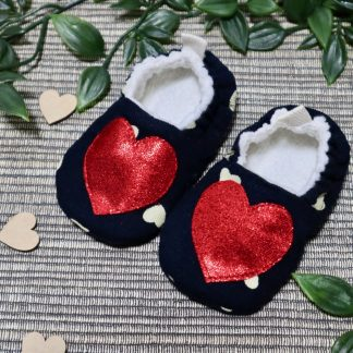 Navy baby shoes with a bright red heart appliqués on the uppers