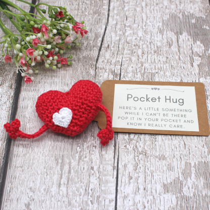 red crochet pocket hug with arms and a label with a sentiment on