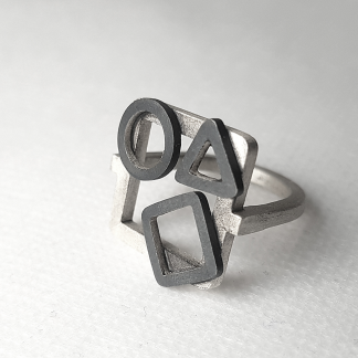 Artisan Geometric Patina Statement Ring in Sterling Silver is displayed on the white surface.