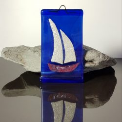 A pretty fused glass, small wall hanging, 'Silver Sails' comes with either a red or a golden hull and glistening silver sails.  Measuring approximately 6.5 cm wide and 11cm tall, it is perfect for that small  space, perhaps in a bathroom or hall way.