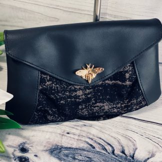 Black evening clutch bag in faux leather and black and gold upholstery weight textured fabric.