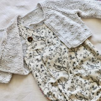 Baby romper in a vintage style cotton fabric featuring birds, flowers & leaves, shown with a grey hand knitted cardigan