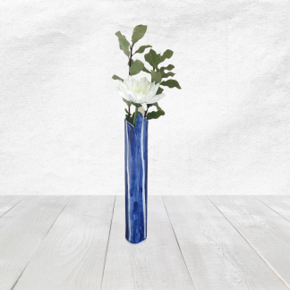 This hand rolled porcelain vase is glazed in the ever popular blue and white colours. It is tall and slim