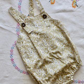 Child's bubble shaped romper in a green ditsy floral print with elasticated leg openings at the thigh and shoulder straps that fasten with 2 dark wooden buttons