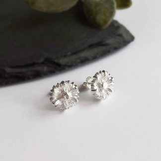 A pair of pretty, handmade, fine silver daisy flower stud earrings, handcrafted by The Tiny Tree Frog Jewellery