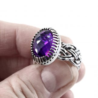 A hand holding a sterling silver ring with basket weave design band and large oval Amethyst