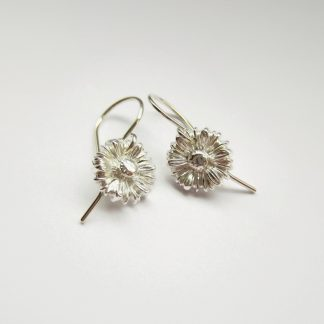 A pair of pretty, handmade, fine silver daisy flower drop earrings, handcrafted by The Tiny Tree Frog Jewellery