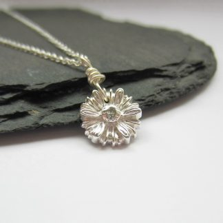 A dainty, handmade fine silver daisy flower pendant necklace, handcrafted by The Tiny Tree Frog Jewellery