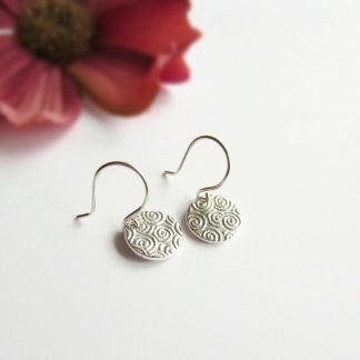 A pair of pretty, handmade, fine silver spiral swirl textured pattern drop earrings, handcrafted by The Tiny Tree Frog Jewellery